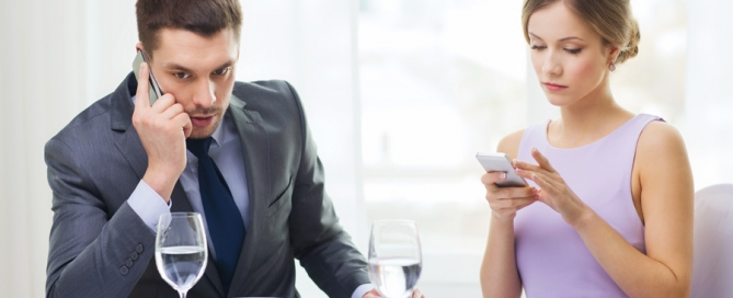 Couple-Using-Smart-Phones-Restaurant